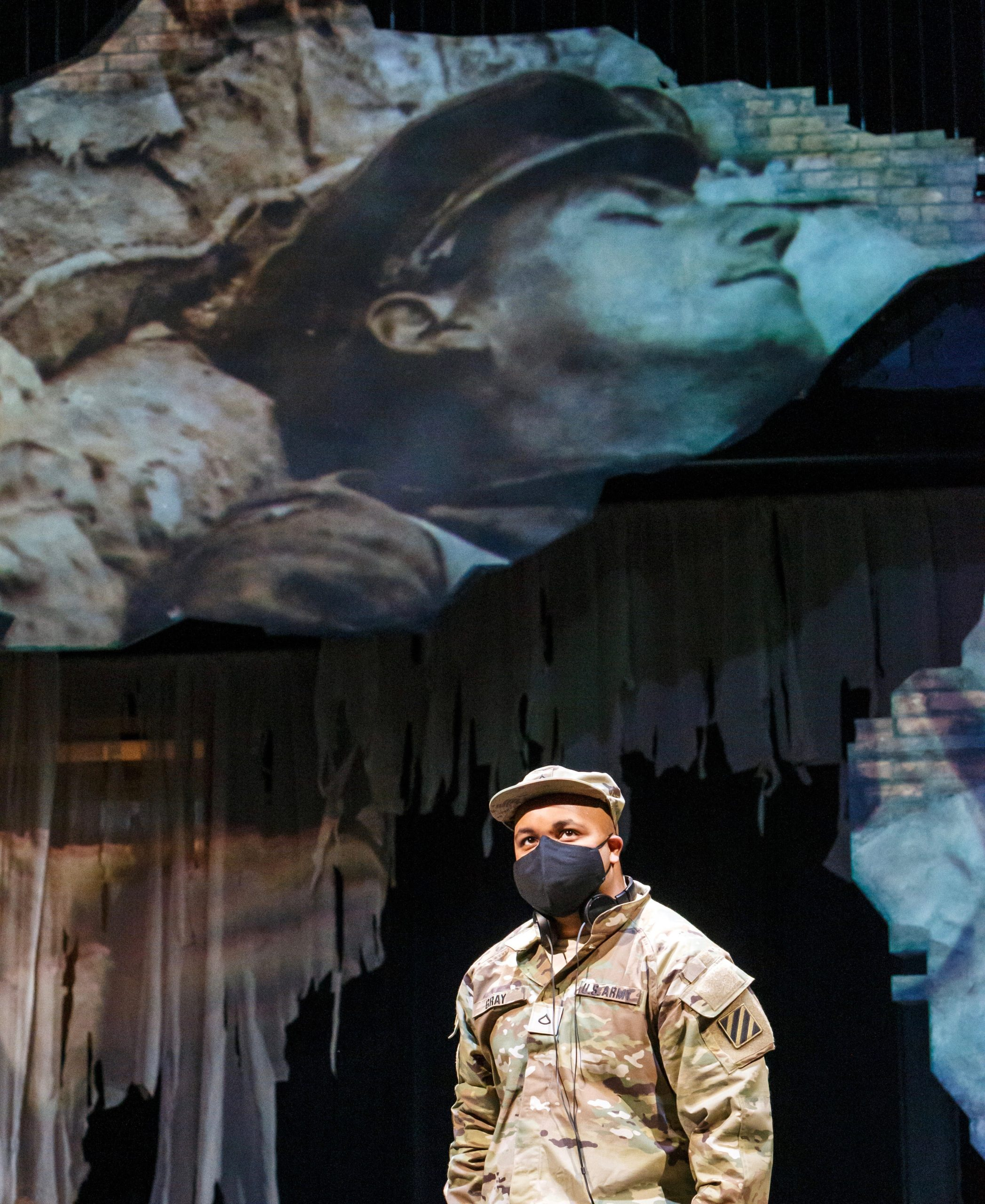 Baritone Yazid Gray soldiers on beneath a looming, projected nightmarish image in Pittsburgh Opera's 'Soldier Songs.' (photo: David Bachman Photography)