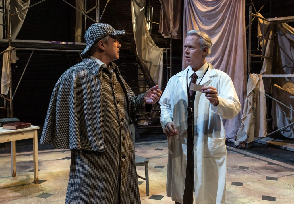 White-coated asylum chief Dr. Evans (Tim McGeever) questions everything, including this decked-out Sherlock's impressive credentials.