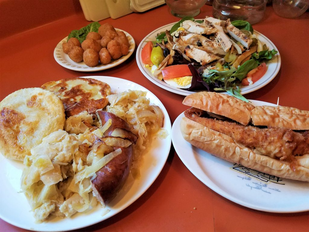 Starlite Lounge food, clockwise from bottom left: Polish Platter, fried mushrooms, Starlite Grilled Chicken Salad, and Starlite Famous Fried Fish Sandwich.