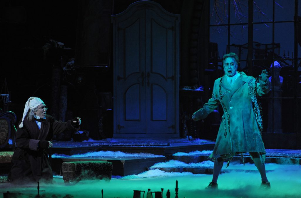 Scrooge (Patrick Page) is visited by a ghost of Christmas (Daniel Krell). Photo: Archie Carpenter.