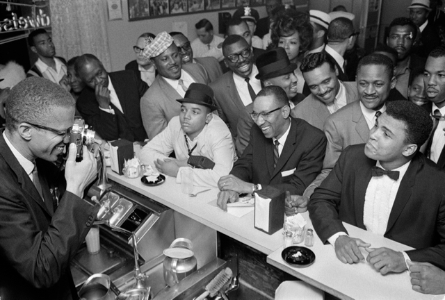 In this real-life scene from the time of the title fight, that's Malcolm X with the camera and Cassius Clay—soon to be Ali—in the tux. (photo: Ira Rosenberg for World Journal Tribune, 1964)