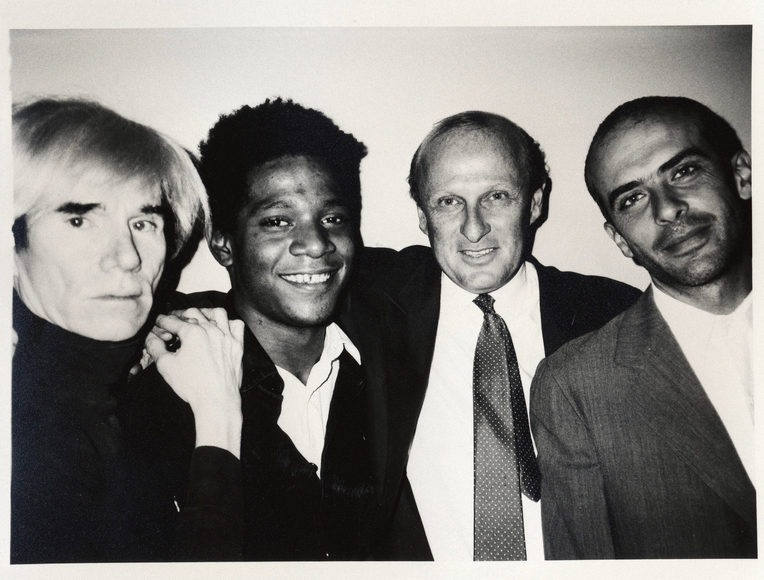Warhol and Basquiat (L) teamed up with artist Francesco Clemente (R) through Bruno Bischofberger, the guy in the tie. (Photo, 1984, Galerie Bruno Bischofberger, shared via CC BY-SA 4.0)