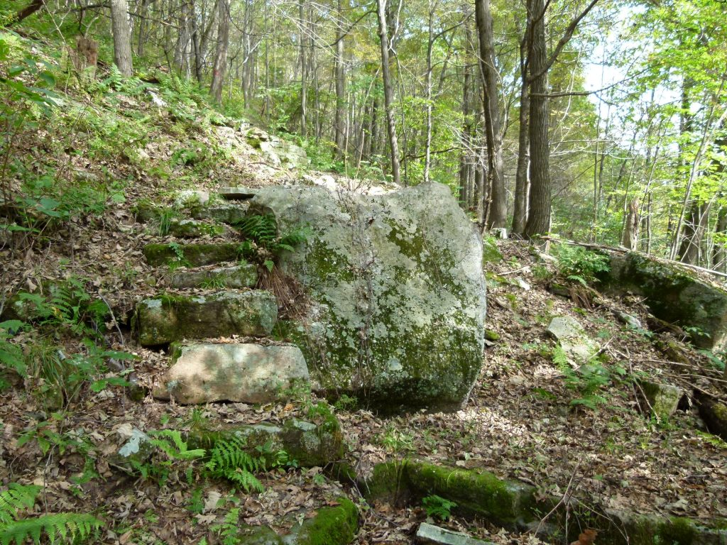 Follow the rock steps up and over the rock outcropping to continue up the mountainside.