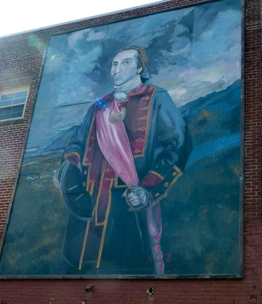 A large mural of Colonel George Washington depicts him during the General Forbes march towards Fort Duquesne. It is on the back of the HeBrews Coffee Company building.