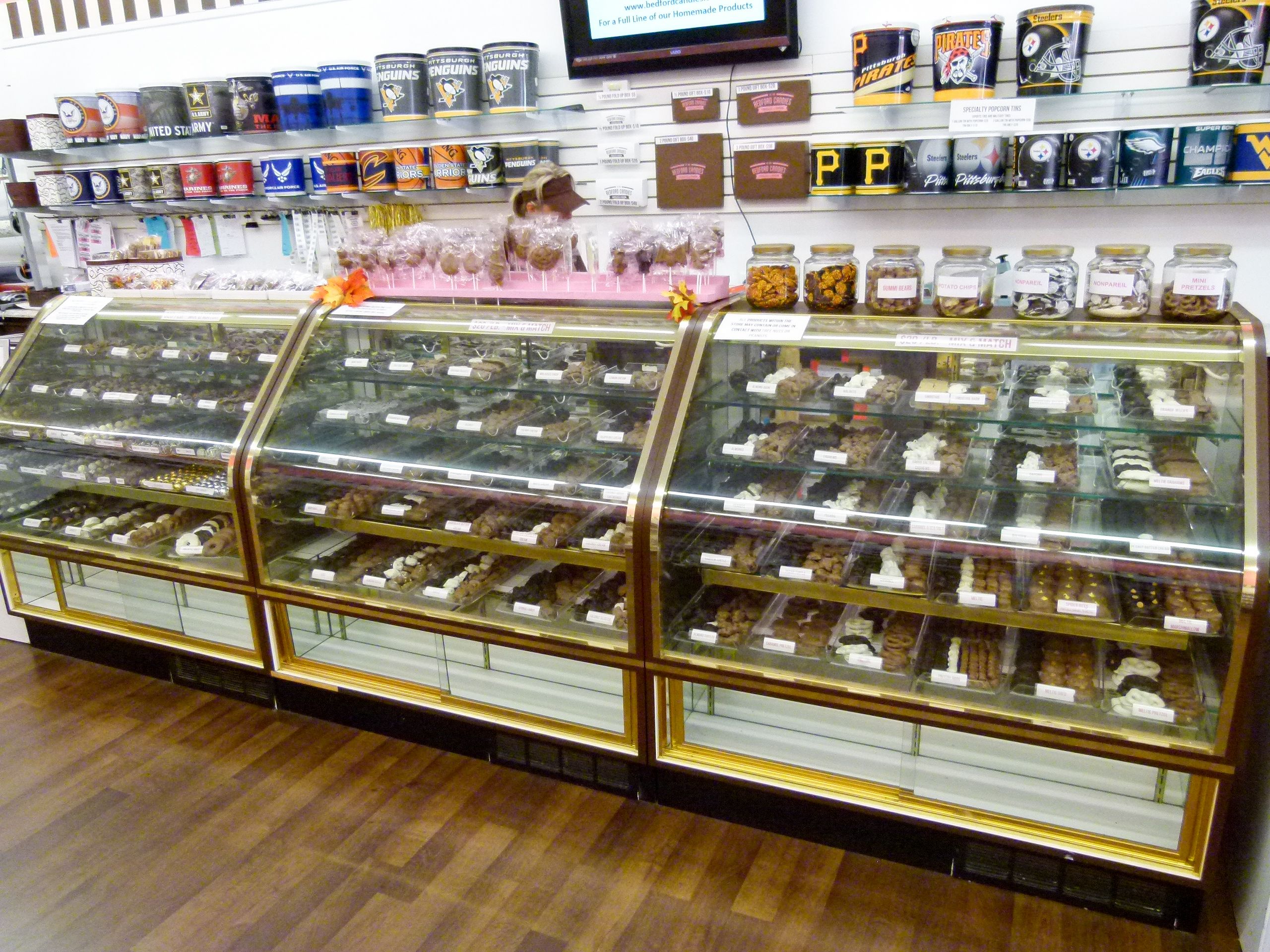 Three cases hold hand-dipped chocolates and truffles. Manger J.D. works on an order behind the counter.
