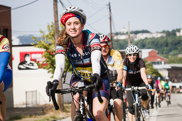 A pack of cyclists bike through the streets of the city during PedalPGH.