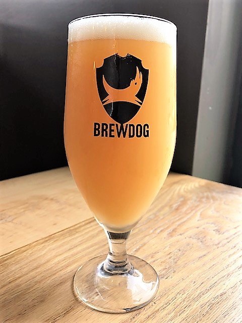 """A crest of a cartoon pup with its head held high jumps over the word """"Brewdog"""" in all caps on a glass of radiant Ladybird: Pink Boots IPA."""