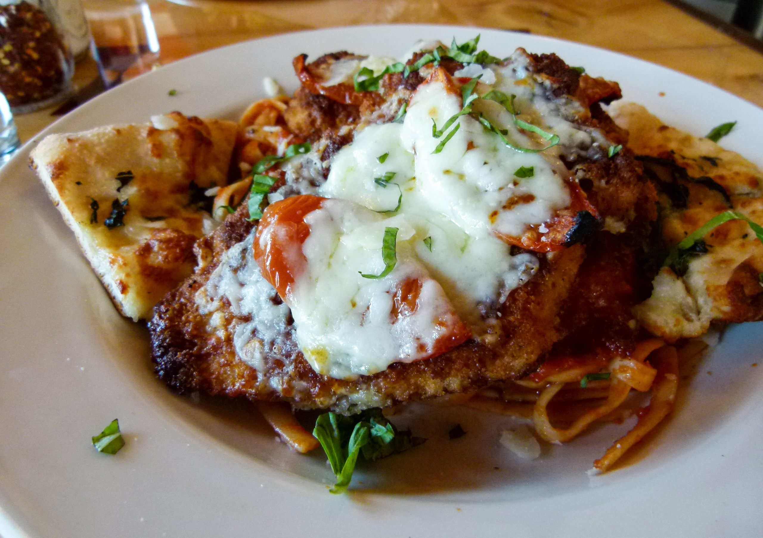 Chicken Parmesan atop fettuccine and flanked by garlic bread.
