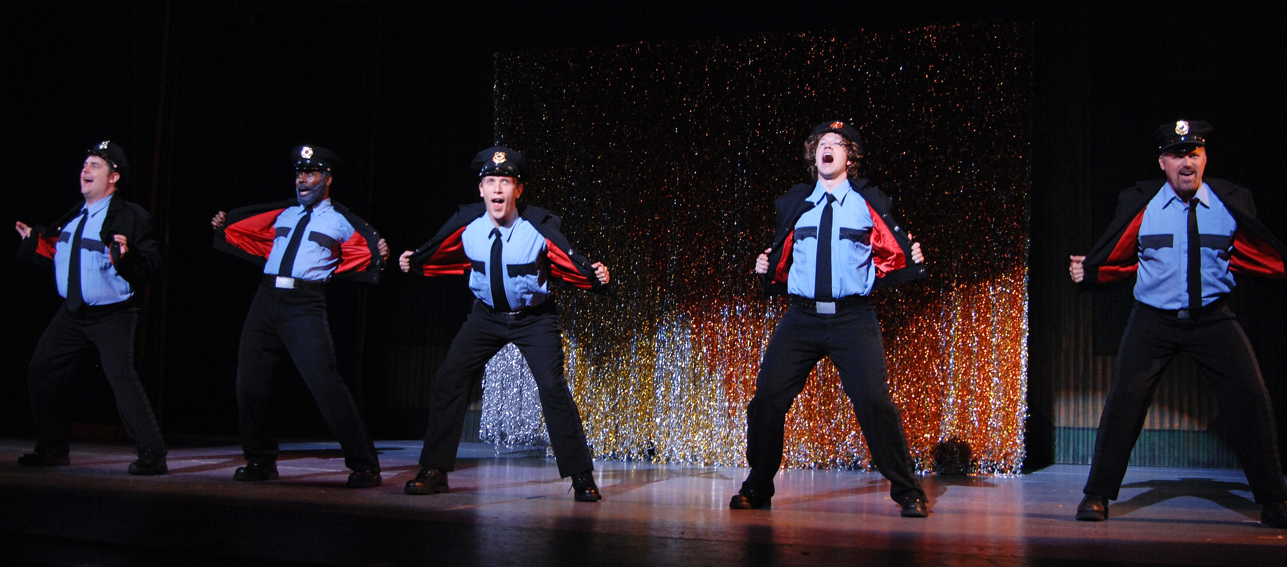 Costumed as cops, the boys are about to show what they're made of in 'The Full Monty.'