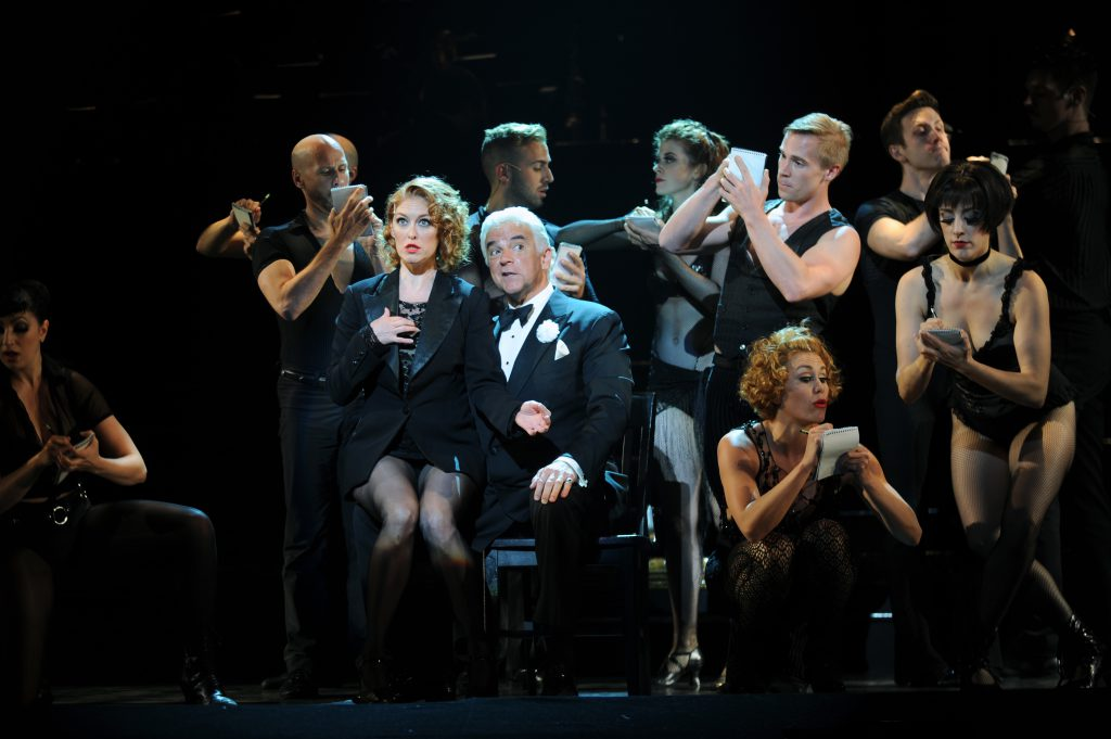Billy Flynn (John O'Hurley) 'guides' Roxie Hart (Dylis Croman) through a pretrial press conference.