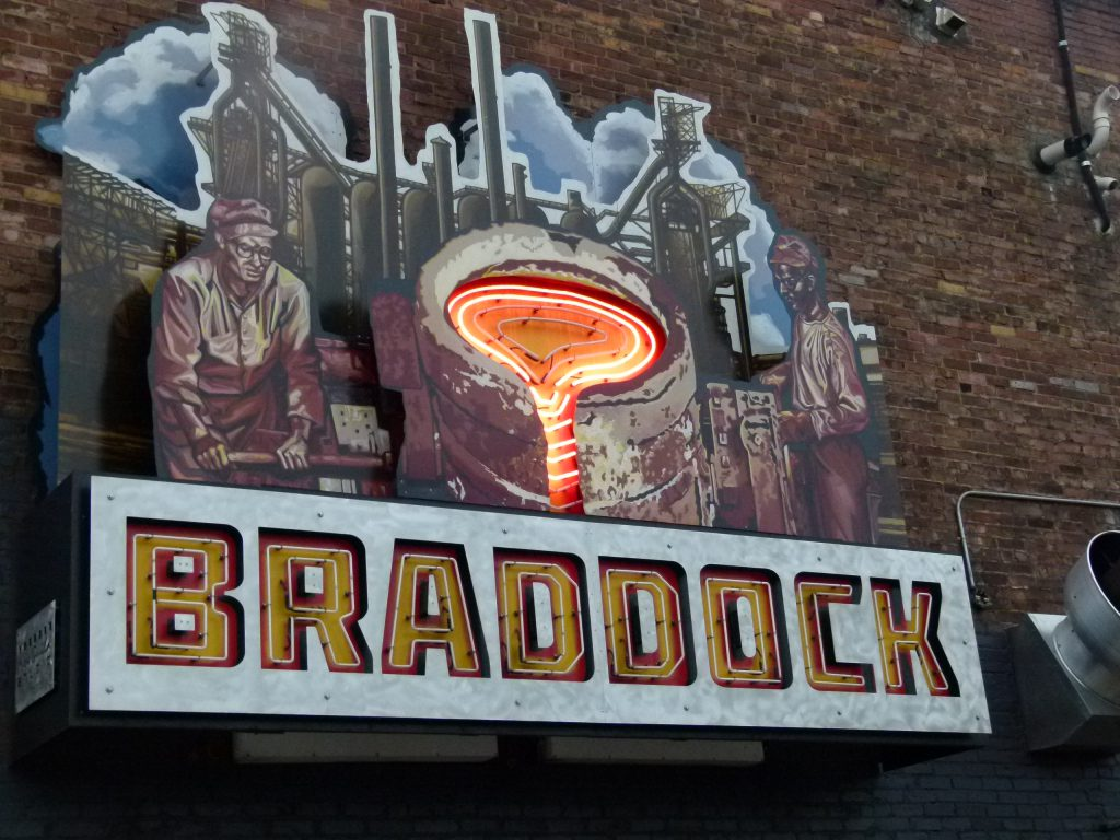 A neon sign highlighting Braddock's steel making history on the side of Superior Motors.