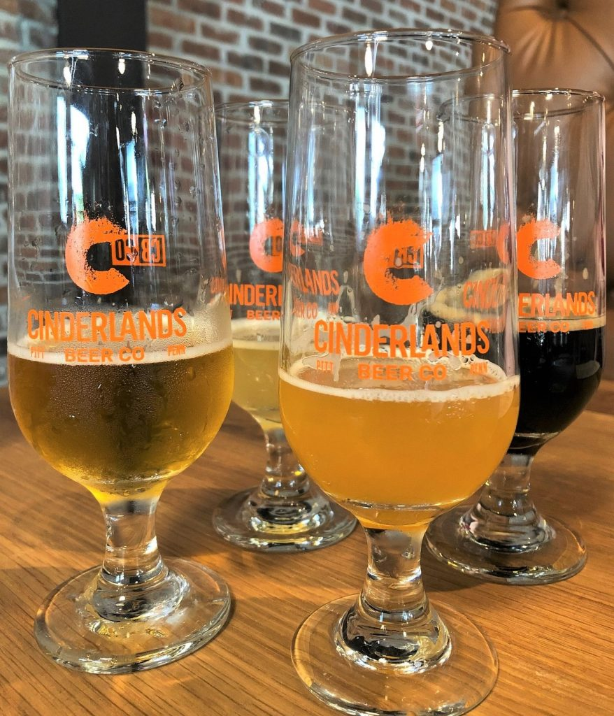 A tasting array composed of (l. to r.) Tracks Again Unfiltered Pilsner, Grizzled Canary Grisette, Range of Light Double IPA, and Bougie Pajamas Tea Brown Ale.