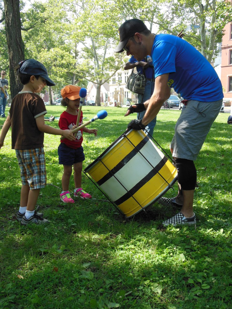 Children accompany a Timbeleza percussionist on the surdo, a type of Brazilian bass drum.
