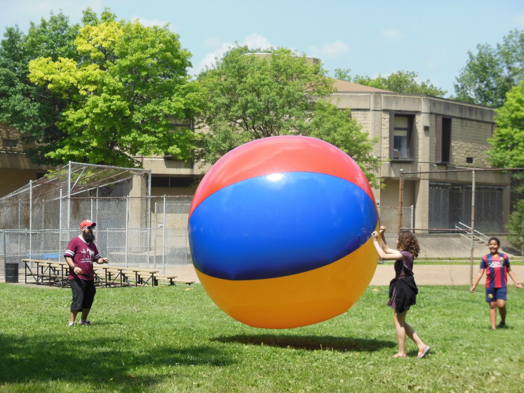 Attendees at Allegheny Commons East bounce the giant beach ball, courtesy of The City of Play, an organization which promotes playful ways for Pittsburghers to engage in their city.