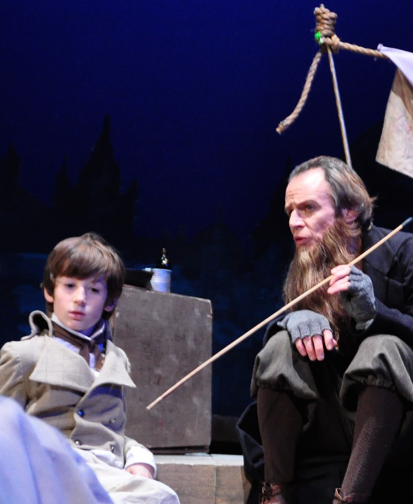 Oliver (Will Sendera) hopes that Fagin will spare the rod.
