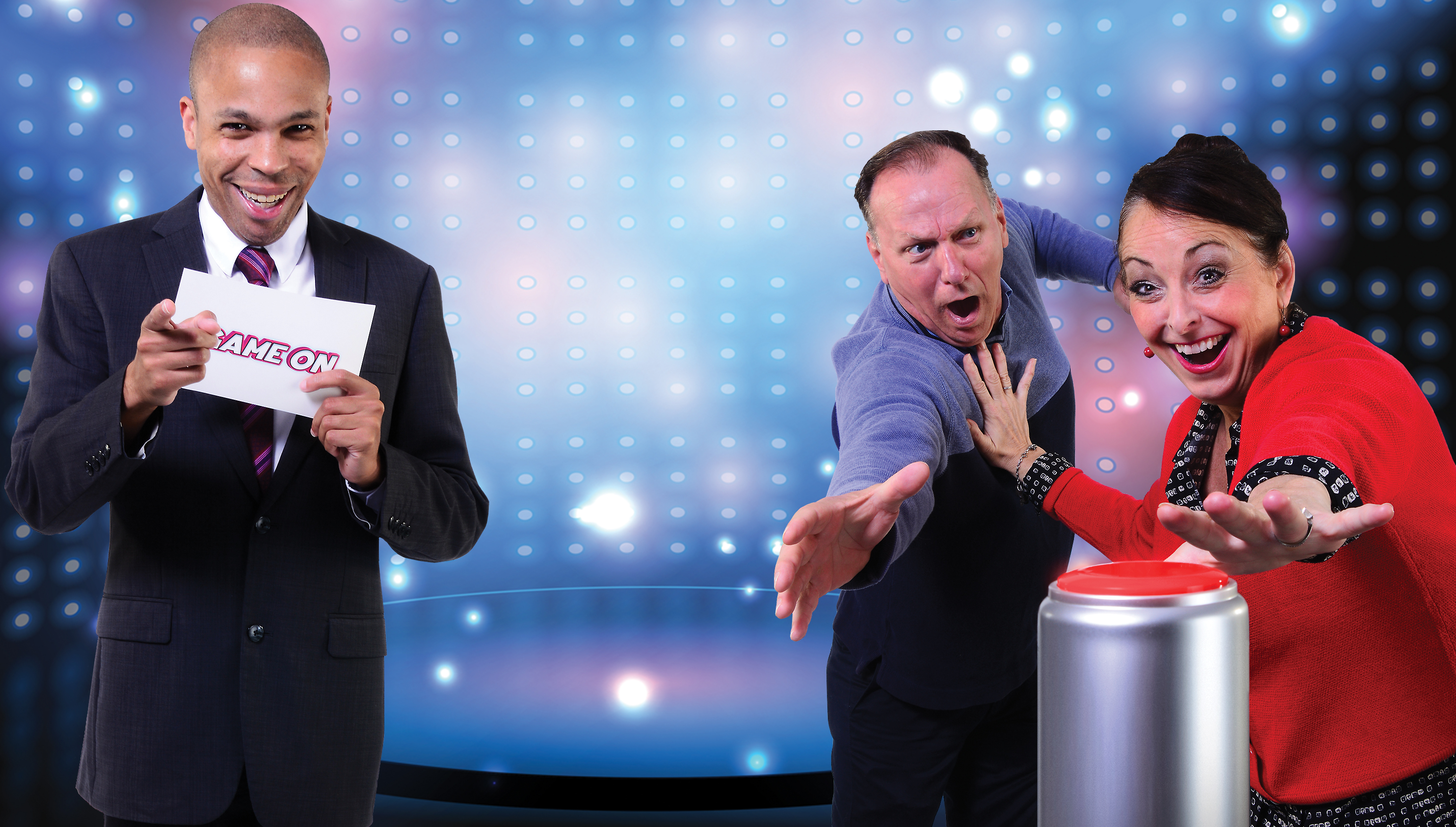 Game show contestants (Tim Brady and Christine Laitta) reach for the big red button as the 'Game On' host (Jason Shavers) runs the contest. (Photo: Archie Carpenter).