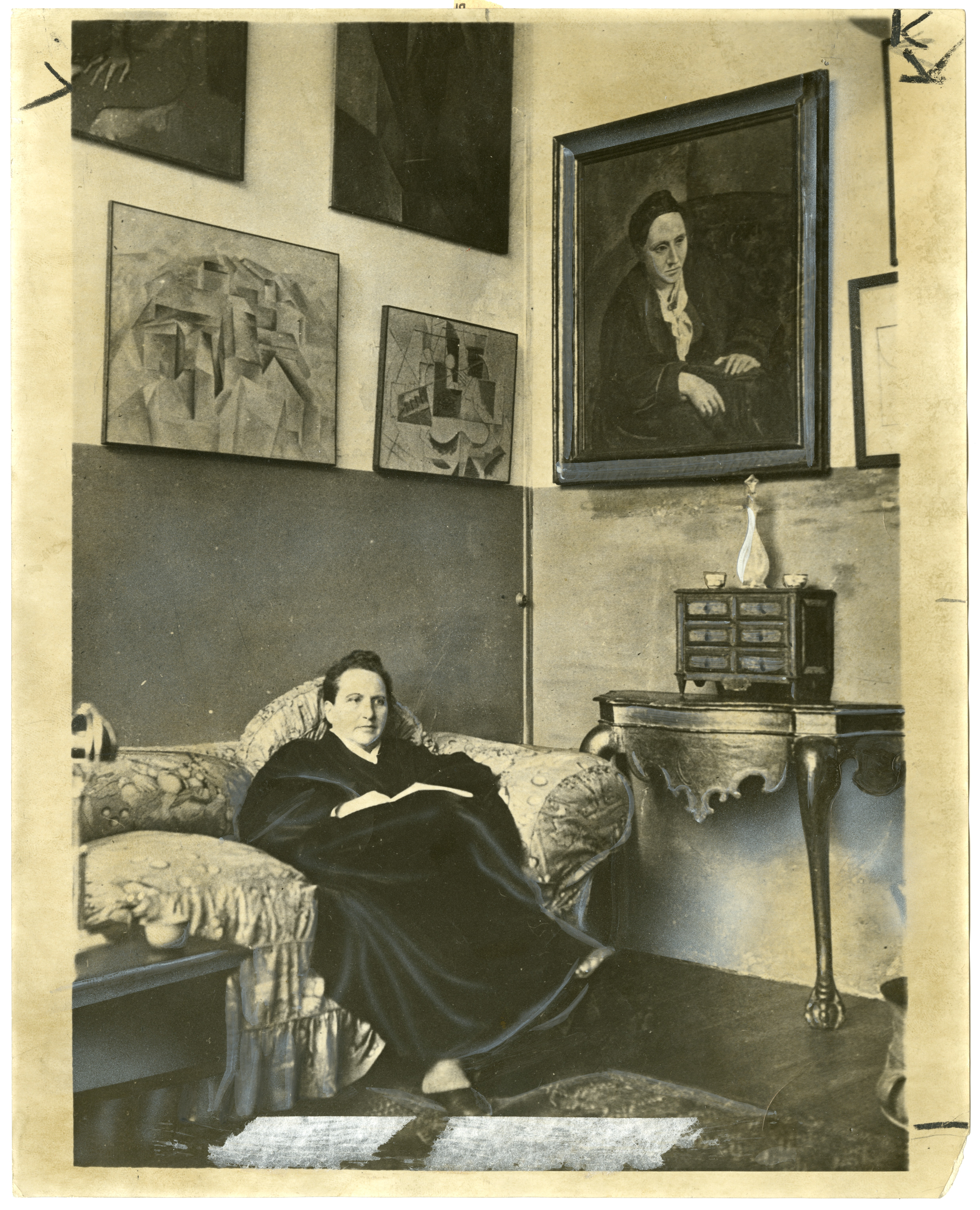 """Gertrude Stein at home under her portrait by Picasso, who is a character in """"Twenty-Seven."""""""