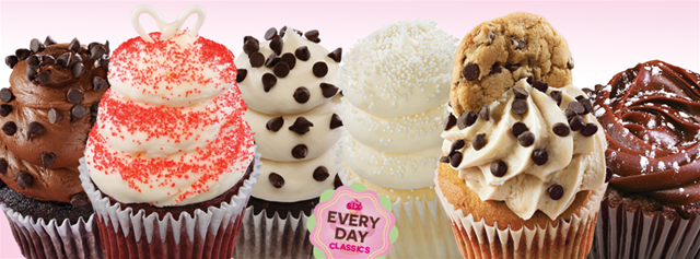 A delicious assortment of Gigi's cupcakes with swirled icing piled high and decorated with tasty chips and sprinkles.
