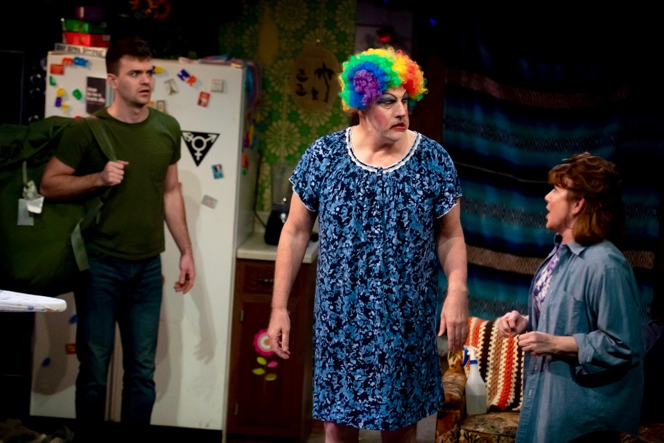 When ex-Marine Isaac returns from combat to find Dad drugged, demented, and decked in drag, he learns that Mom has launched a revolution on the home front. The actors (L to R) are Tad Cooley, Douglas Rees, and Helena Ruoti.