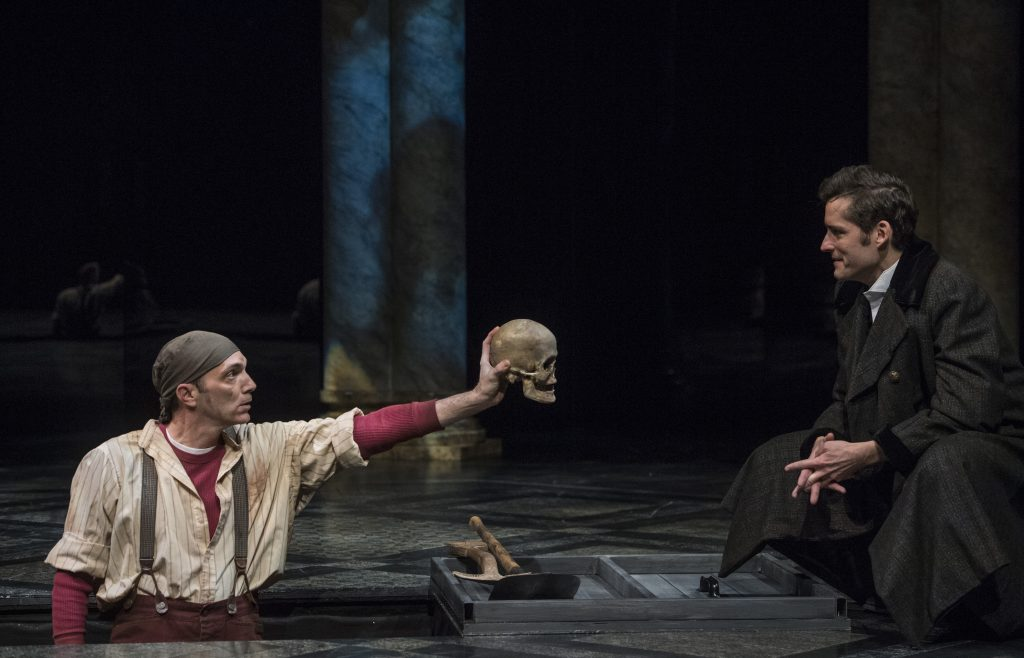 1st Gravedigger (Tony Bingham) shows Hamlet the skull of the deceased court jester Yorick.
