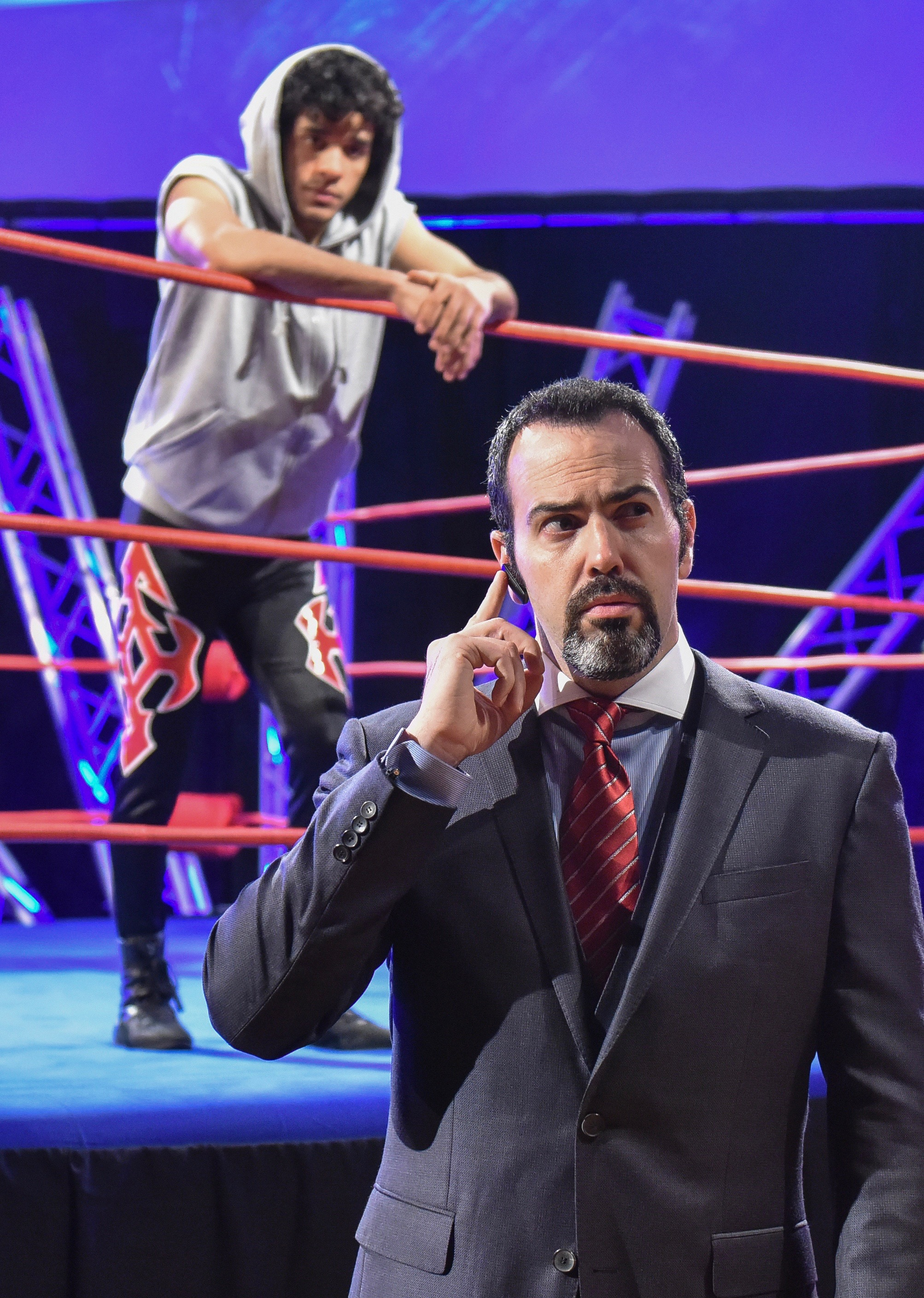 Promoter Everett K. Olson (Patrick Jordan) is the operator who pulls the strings, while Mace (Perez-Abraham, background) awaits his next move.