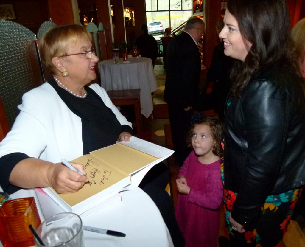 Grace from Cleveland looks in awe at Lidia while Lidia signs a children's book for her and talks with her mom Natalie Kupinski.