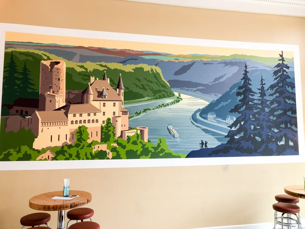 A vibrant mural of Germany's Rhine River Valley enlivens a wall in the beer hall.