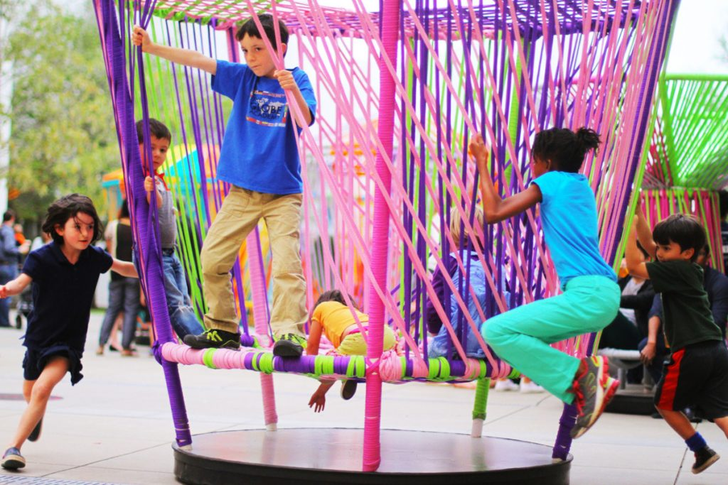 Kids enjoy playing on Los Trompos, colorful spinning tops, by Mexican artists Héctor Esrawe and Ignacio Cadena.