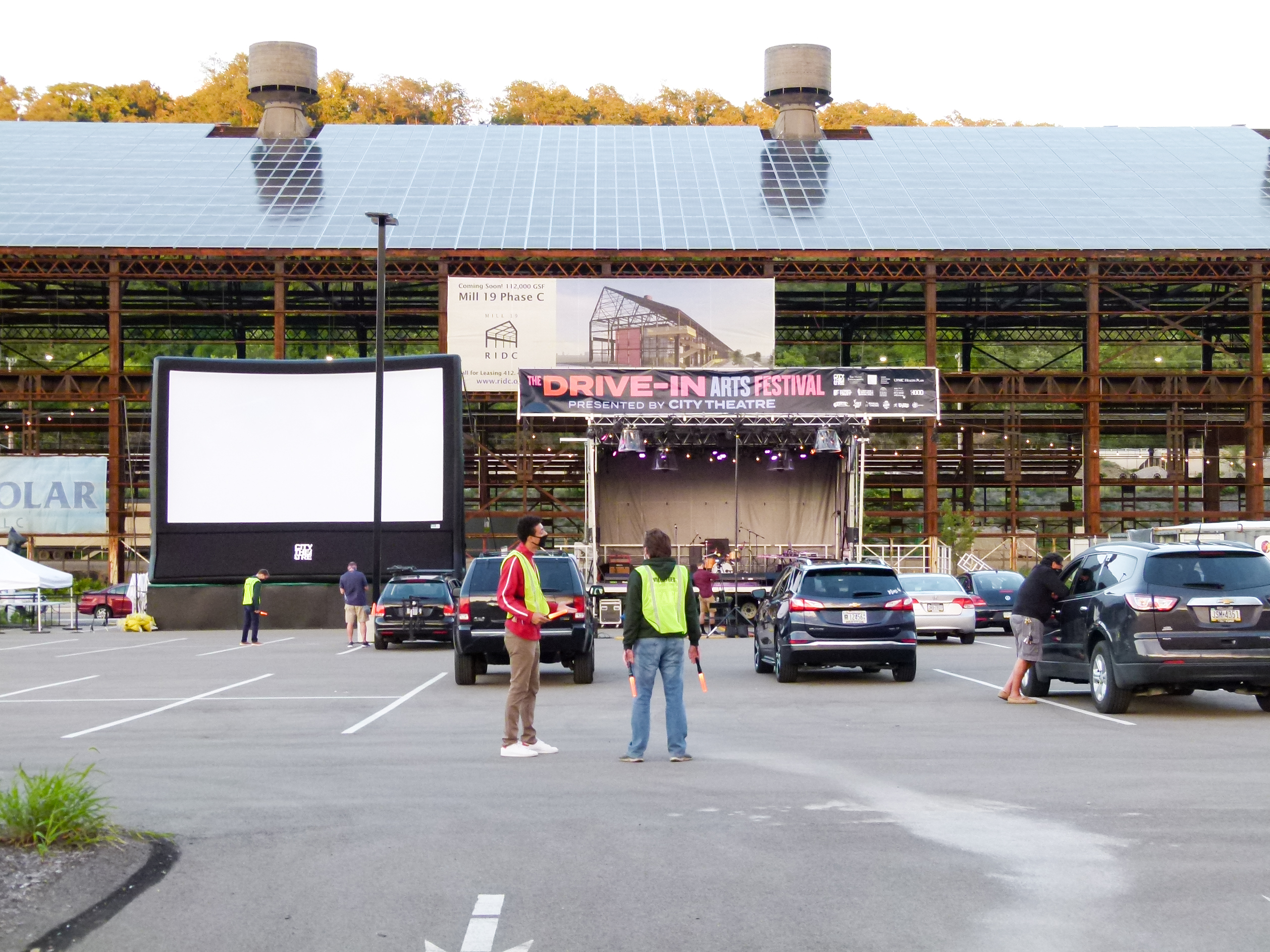 The Drive-in Arts Festival set against the backdrop of Mill 19 just as cars are starting to enter.