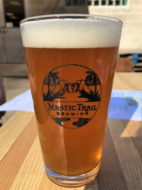 Two parrots clink beer glasses on Mastic Trail's logo, emblazoned on a glass of Hazy Jones IPA.