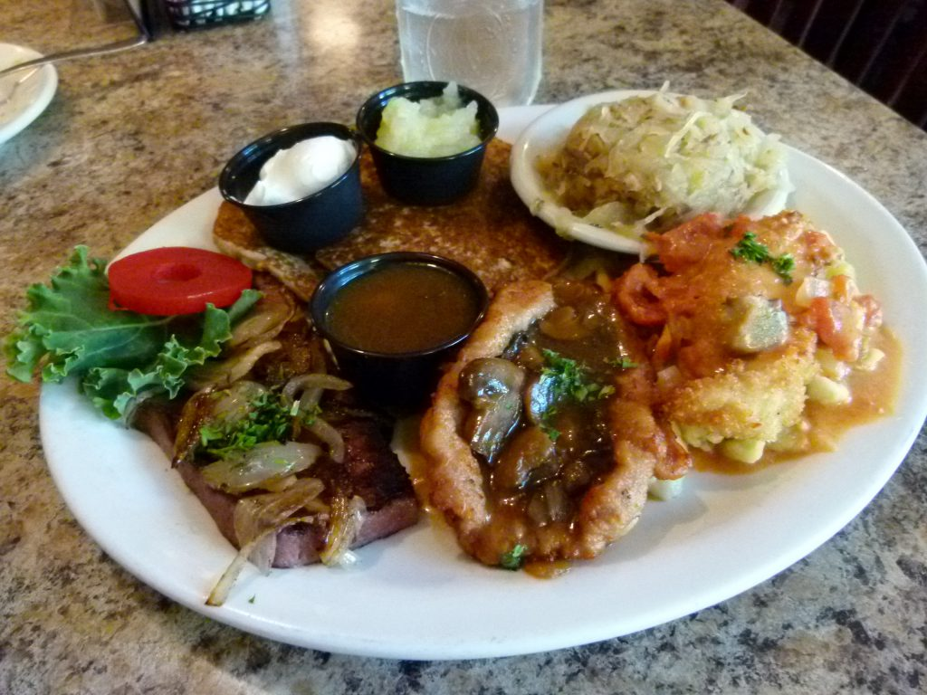 Max's Sampler Platter with (l. to r.) leberkase, jäger schnitzel, and chicken Viennese. Sides are potato pancakes and sauerkraut.