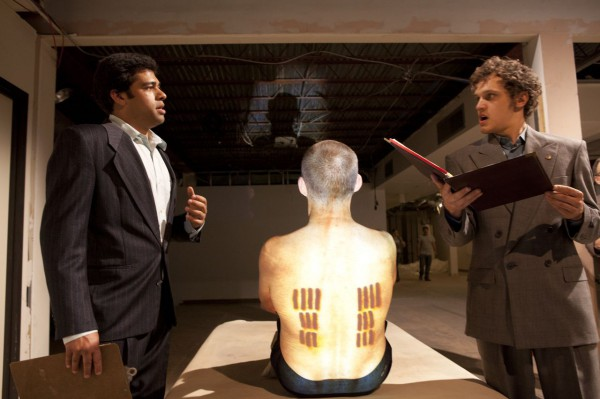 What do the tattoos signify?  Scholars (Anand Nagraj, left, and Antonio Marziale) expound their views while the Iceman (Malcolm Tulip) displays the evidence.