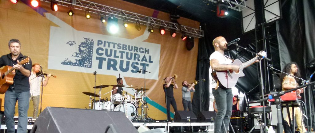 Nahko and Medicine for the People performing on the Dollar Bank Main Stage. Band members: (l. to r.) Chase Makai, Tim Snider, Justin Chittams, Max Ribner, TJ Schaper, Nahko Bear, and Patricio Zuñiga Labarca.