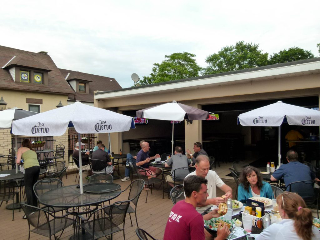 Diners enjoying an evening meal on the second floor patio deck of the Oakmont Tavern.