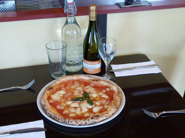 Pizza served tableside with water and wine.