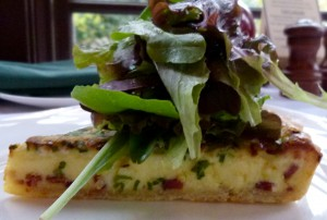 Green onion and bacon quiche topped with spring mix from The Frick's greenhouse.