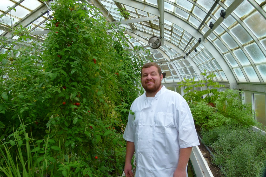 Chef Seth Bailey in The Frick greenhouse next to tomato plants and happy that he has fresh local tomatoes year round.