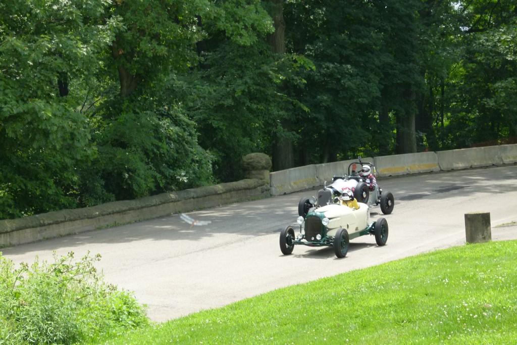 Two older vintage, open-wheel racers jockey for position.