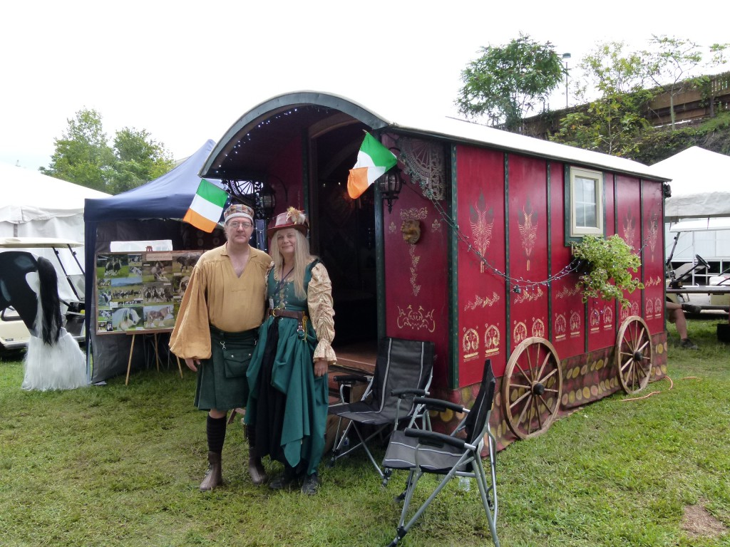 Dressed in period garb, James Rumbaugh and Lynette Garlan stand in front of an Irish caravan.