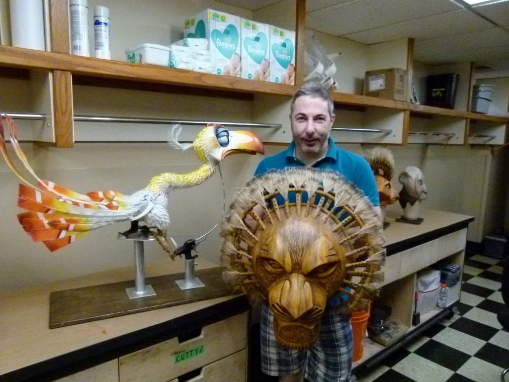 Puppet master Michael Reilly with his favorite mask, Mufasa, with the Zasu puppet looking on.