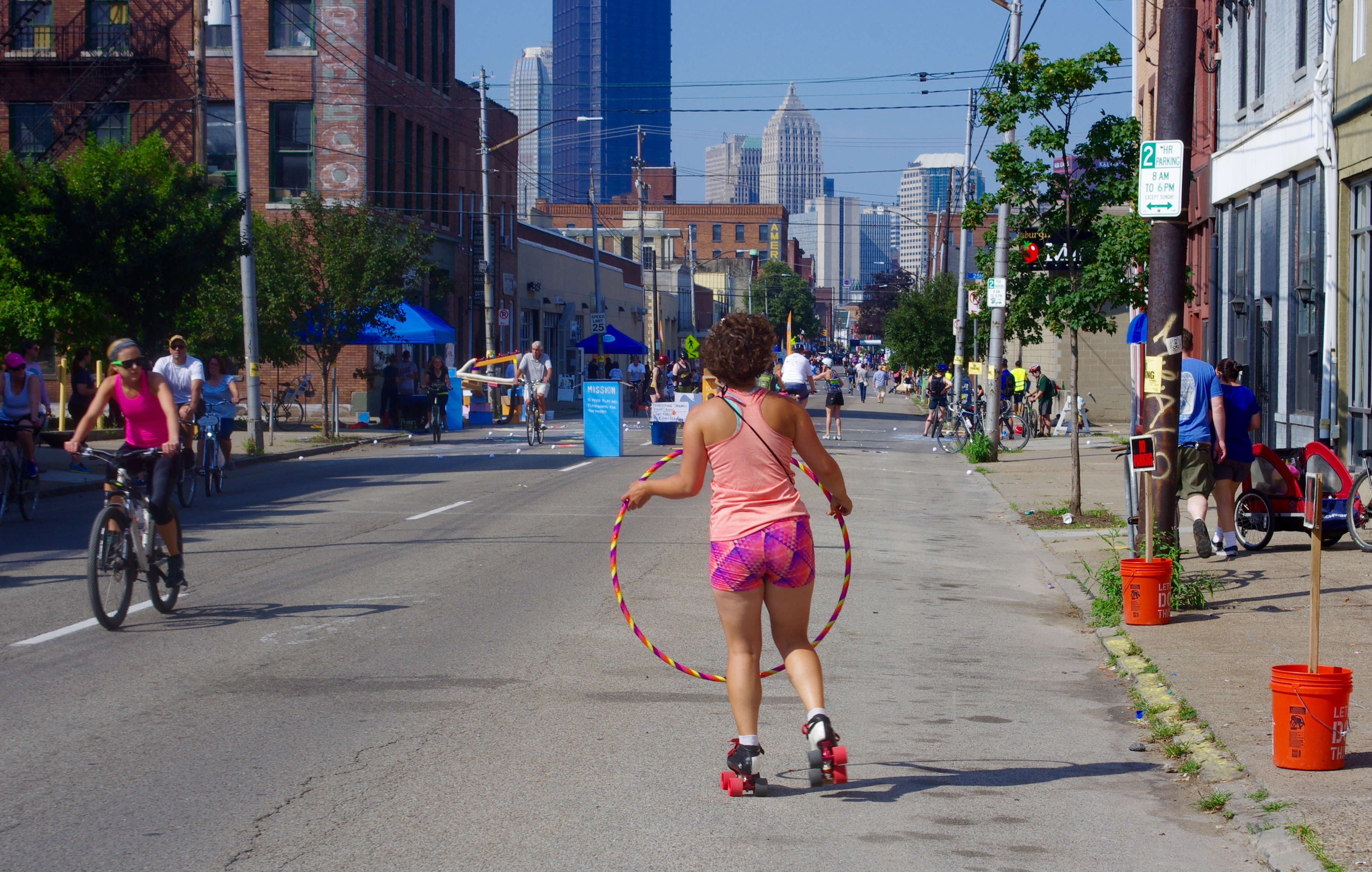 Holly Miller hula hoops while roller skating towards downtown.