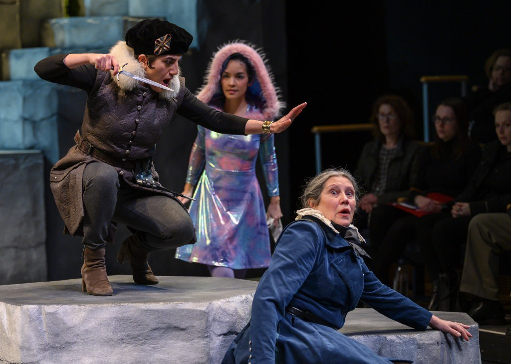 Homicide is prevented when Ariel, wearing an enchanted hoodie, magically intervenes. Wicked Sebastian (left) is played by Aryana Sedarati, Ariel by Janelle Velasquez, and good Gonzalo by Laurie Klatscher.