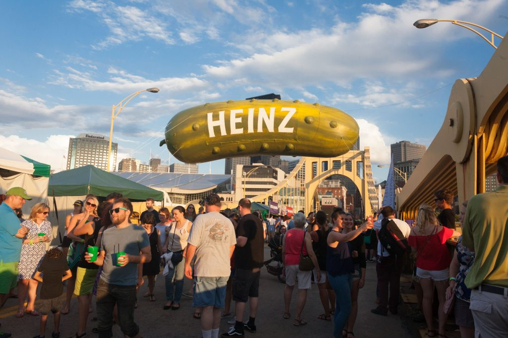 The Picklesburgh giant inflatable Heinz pickle proudly flies above attendees on the Roberto Clemente Bridge.
