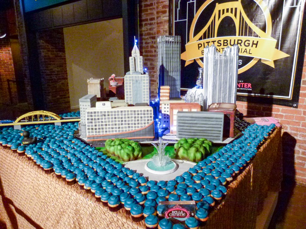 "A beautiful cake of Pittsburgh. Notice the crystalline sugar ""water"" emerging from the fountain and the Heinz History Center with it's Heinz Ketchup bottle in the background."
