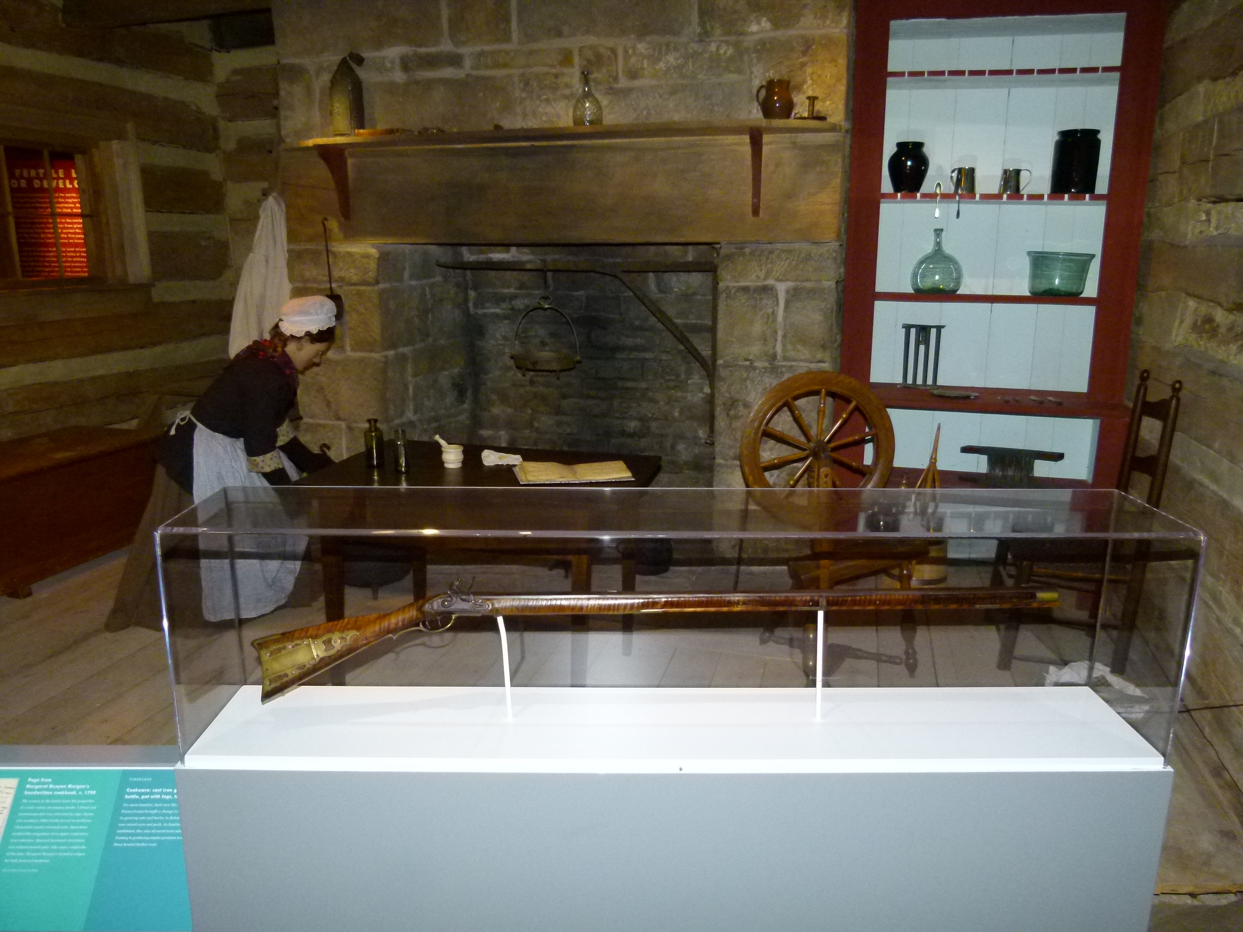 An early American home interior with a hearth, spinning wheel, and long gun.