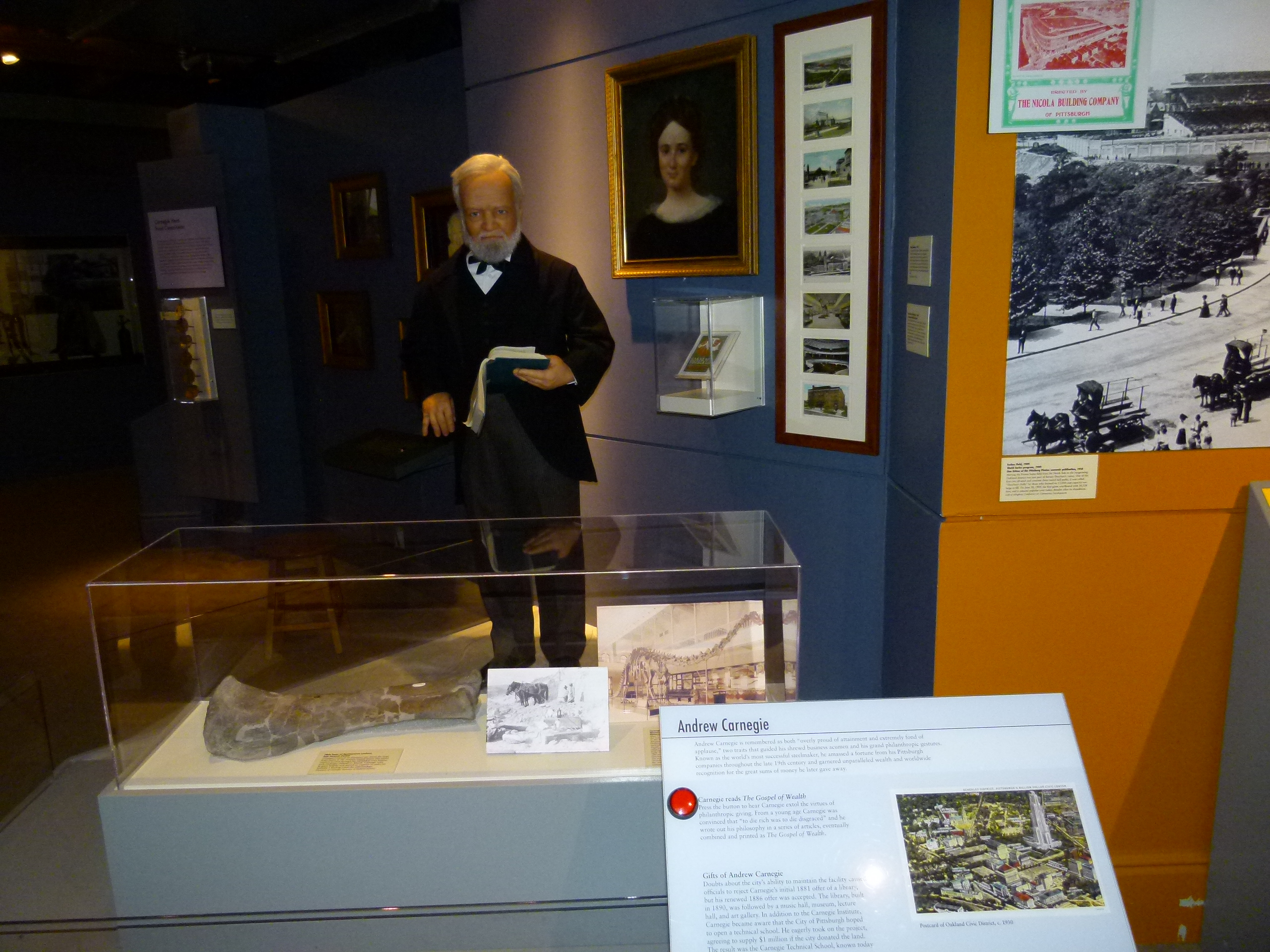 Pittsburgh industrialist Andrew Carnegie standing behind a dinosaur bone he funded the discovery of, and holding a book to signify his creation of Carnegie free Libraries.