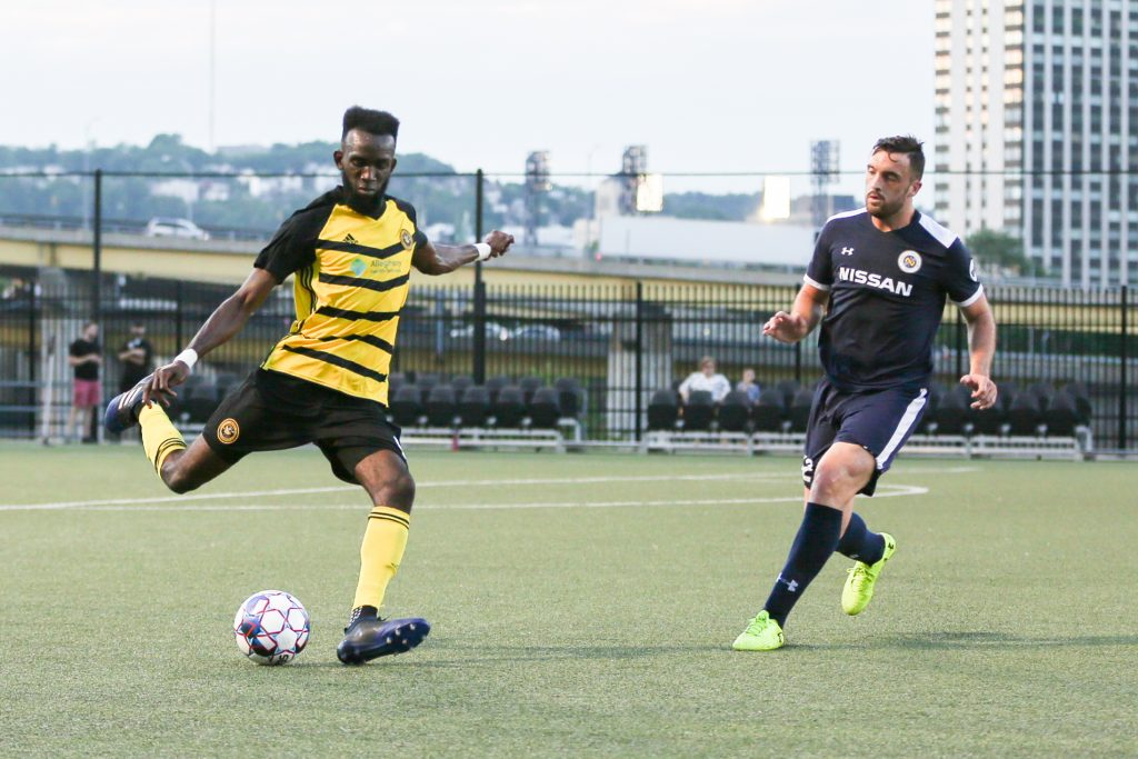 A Riverhounds forward takes a shot on goal as a defender closes fast. Photo: Chris Cowger.