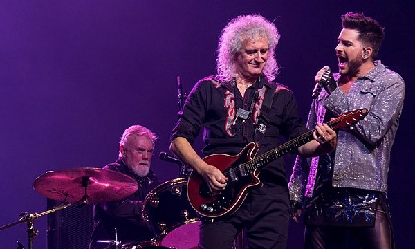 Queen and Adam Lambert in a 2017 Concert. (L. to r.) Roger Taylor, Brian May, and Lambert. (photo: Raph_PH and Wikipedia)
