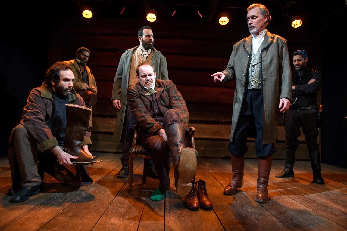 If the boot fits, fear it! Villainous Walter Brown (Cotter Smith, standing, front) explains to poor Wings (Connor McCanlus), center) why the tea stains on a pair of tea-colored boots are grounds for a duel to the death.