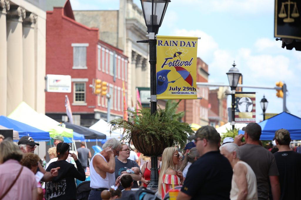 It's very unusual, but everyone attending this event is hoping that it will rain. After all, it is the Rain Day Festival in Waynesburg. Notice the banner with the Festival's very cool mascot Wayne Drop. (photo: Rain Day Festival and Waynesburg borough)